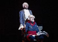 Mężczyzna siedzący na krześle, w peruce i epokowym stroju z laska w ręce raz drugi stojący za nim również w peruce i epokowym stroju