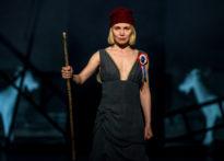 Kobieta w sukni z rozetą przypiętą do piersi trzymająca w ręku patyk, za nią stojący pozostali aktorzy.