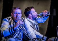 Dwóch mężczyzn siedzących na scenie, pijących napój z szklanych butelek.