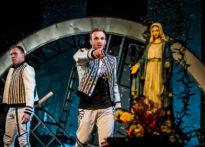 Dwóch aktorów stojących na scenie, jeden wskazuje palcem w stronę publiczności, drugi trzyma w ręku siekierę. W tle figura Matki Bożej