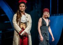 Dwie kobiety stojące na scenie, jedna w sukience, druga w surducie i czerwonych spodniach.