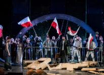 Aktorzy stojący za barykadą trzymających w ręce biało- czerwone flagi. Zdjęcie zbiorcze