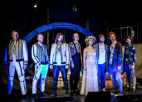 Aktorzy stojący na scenie w niebieskim świetle na tle scenografii