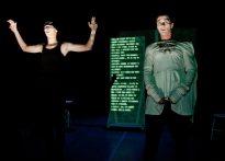 Dwóch aktorów, jeden w czapce i czarnym podkoszulki oraz drugi w białej sukience, Za nimi na elemencie scenografii wyświetlają się napisy. Na zdjęciu Piotr Dąbrowski oraz Paweł Siwiak