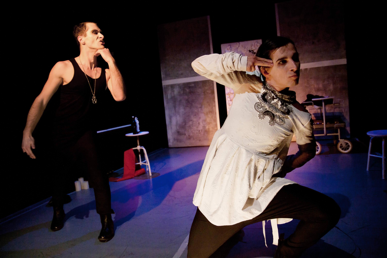 Na pierwszym planie aktor klękający na jedno kolano z dwoma palcami przy skroni, na drugim planie aktor z ręką pod brodą w trakcie mówienia kwestii. Na zdjęciu Piotr Dąbrowski oraz Paweł Siwiak