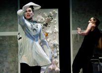 Aktor w białej sukience wymachujący ręką z rozmazaną szminka na ustach, w tle scenografia z pluszowymi misiami oraz odsuwający się drugi aktor. Na zdjęciu Piotr Dąbrowski oraz Paweł Siwiak.