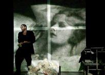 Aktor osuwający sie na podłogę z laką Barbie w ręce na tle ekranu na którym wyświetla się twarz kobiety. Na zdjęciu Piotr Dąbrowski