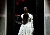 Aktor na czarnym tle ubrany w białą sukienkę trzymając w jednej ręce misia a w drugiej czarne pudło oraz czerwone balony. Na zdjęciu Paweł Siwiak