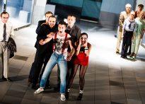Zdjęcie grupowe ze spektaklu Piszczyk - na pierwszym panie grupa aktorów wyraźnie czymś podekscytowanych, w tle aktorzy stojący spokojnie