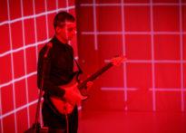 Aktor z gitarą elektryczną na tle czerwonej ściany w kratkę
