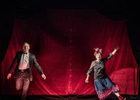 Dwóch aktorów uchwyconych w pozie tanecznej na czerwonym tle. Na zdjęciu Piotr Kaźmierczak oraz Barbara Krasińska.