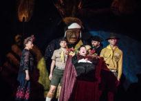 Pięciu aktorów na ciemnym tle, za plecami aktorów stoi kukła prezentująca czarnoskóra postać. Na pierwszym planie aktora leżąca w trumnie. Na zdjęciu Barbara Krasińska, Sylwia Zajkowska, Jakub Papuga, Paweł Siwiak, Elżbieta Węgrzyn.
