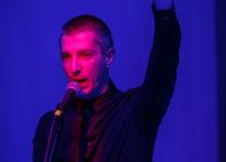 Mężczyzna stojący przy mikrofonie z ręką uniesioną do góry