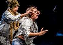Dwie kobiety stojące na scenie gdzie jedna stoi okrakiem a druga za nią oplata jej głowę rękoma