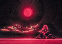 Siedząca kobieta na tel głów chóru wychodzących ze scenografii