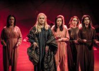 Aktorki w epokowych strojach na tle czerwonej scenografii
