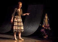 Aktorka stojąca na scenie wskazująca figurę Matki Bożej.