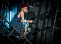 Aktorka w sukience siedząca na metalowej konstrukcji scenografii.