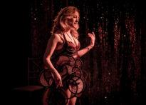 Aktorka w skąpej bieliźnie stojąca bokiem na tle brokatowej kotary. Na zdjęciu Barbara Prokopowicz