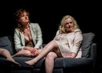 Dwie kobiety w rożnych pozycjach siedzące na kanapie