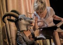 Aktora siedząca na krześle czytająca książkę, aktorka z głową kozła na głowie. Na zdjęciu Barbara Prokopowicz oraz Kornelia Trawkowska