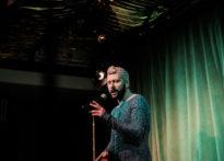 Śpiewający aktor w zielonej cekinowej sukience przy mikrofonie, Na zdjęciu Jakub Papuga