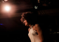 Aktora w świetle reflektora w przezroczystej sukience oraz bogato zdobionym biustonoszu. Na zdjęciu Sylwia Achu