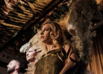 Na pierwszym planie aktorka ubrana w złotą zbroję ze skrzydłami, na drugim planie dwóch aktorów. Na zdjęciu Barbara Prokopowicz, Przemysław Chojęta oraz Jakub Papuga