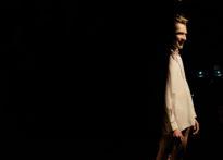 Aktor ubrany tylko w białą koszulę, delikatnie zasłonięty. Na zdjęciu Piotr Dąbrowski