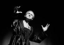Aktor ubrany w porannik stojący na scenie.Zdjęcie czarno białe. Na zdjęciu Wiesław Zanowicz