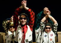 Aktorzy stojący wśród kartonów z rękoma podniesionymi do góry