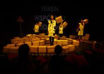 Aktorzy wśród kartonów na scenie