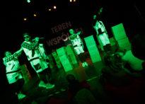 Aktorzy stojący na scenie wśród kartonów w zielonym świetle