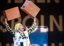 Aktorka stojąca na scenie z kartonami w rękach