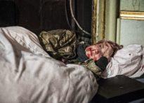 Leżąca aktorka ubrana w kurtkę moro z zakrwawioną twarzą
