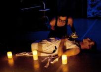 Aktor w okularach i czarnym podkoszulku nachyla sie nad leżącym aktorem z kwiatem w ręce. Przed leżącym aktorem stoją świece. Na zdjęciu Paweł Siwiak oraz Piotr Dąbrowski