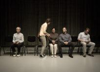 Czworo aktorów siedzących na krzesłach , jednak aktorka stoi i pokazuje coś pozostałym.