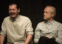 Dwóch siedzących mężczyzn, jeden sie uśmiecha drugi jest poważny. Na zdjęciu Przemysław Chojęta oraz Wiesław Zanowicz