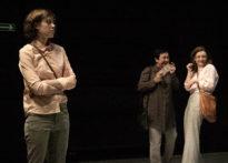 Na pierwszym planie stojąca aktora z poważną miną, na drugim dwie stojące i śmiejące się aktorki.