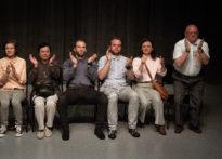 Sześć osób siedzących na krzesłach i bijących brawo