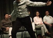 Czworo aktorów siedzących na krzesłach, jeden aktor stojący w otwartej pozie.