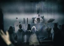 Aktor odbijający się w lustrze wznoszący ręce do góry, w tle wyświetlający się film na ścianie