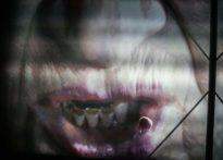 Wyświetlona na ścianie buzia, zbliżenie na nos, usta i zęby. Odbijający