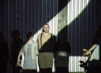 Aktorzy w smudze światła stojący na scenie