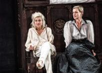 Dwie kobiety siedzące na siedzisku starej szafy.