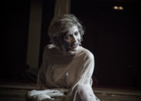 Aktora ubrana w prześwitującą suknię z ubrudzoną twarzą siedząca na scenie