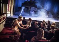 Aktor z zasłoniętymi oczyma, stojący koło publiczności