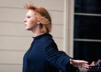 Aktorka z rozwianymi włosami i rozłożonymi rękoma stojąca na scenie