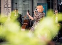 Aktorka w ciekawej pozie śpiewająca do mikrofonu- w tle zespół muzyków