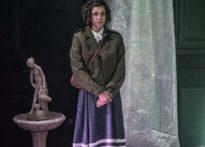 Kobieta ubrana w zieloną marynarkę i granatowa spódnicę za kolano, stojąca na tle fontanny